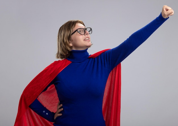Confident young blonde superhero woman in red cape wearing glasses standing in superman pose looking at her fist isolated on white wall