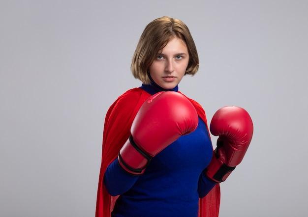 白い壁で隔離の正面を見てボックス手袋を着用して赤いマントで自信を持って若い金髪のスーパーウーマン