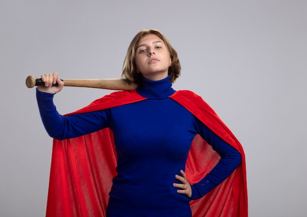 Fiduciosa giovane superdonna bionda in mantello rosso che tiene la mazza da baseball tenendo la mano sulla vita guardando la parte anteriore isolata sul muro bianco