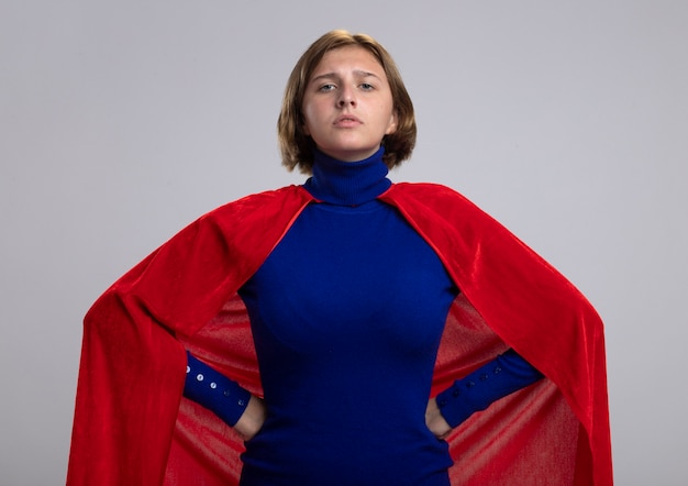 Fiduciosa giovane superdonna bionda in mantello rosso mantenendo le mani sulla vita guardando la parte anteriore isolata sul muro bianco