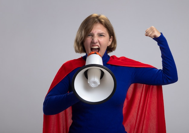 Confident young blonde superwoman in red cape looking at front doing strong gesture shouting in loud speaker isolated on white wall