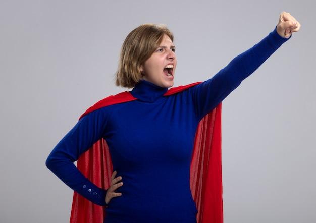 Fiduciosa giovane superdonna bionda in mantello rosso che alza il pugno in piedi nella posa di superman guardando il lato isolato sulla parete bianca