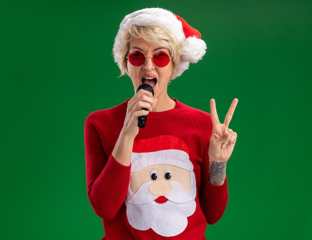 Confident young blonde woman wearing christmas hat and santa claus christmas sweater with glasses talking into microphone looking  doing peace sign isolated on green wall with copy space