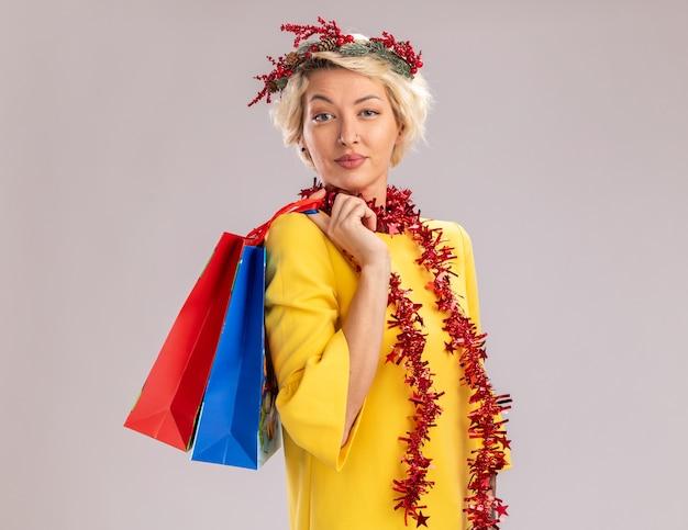 Уверенная в себе молодая блондинка в рождественском венке и гирлянде из мишуры на шее, стоя в профиль, держа рождественские подарочные пакеты на плече, глядя изолированно на белой стене с копией пространства