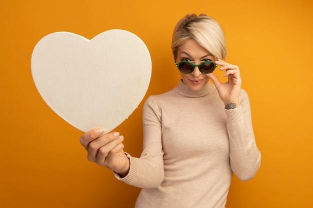 Fiducioso giovane donna bionda che indossa occhiali da sole afferrandoli che si allunga a forma di cuore verso la parte anteriore guardando la parte anteriore isolata sulla parete arancione