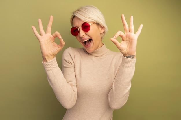 올리브 녹색 벽에 격리된 확인 표시를 하고 앞을 바라보는 선글라스를 쓴 자신감 있는 젊은 금발 여성