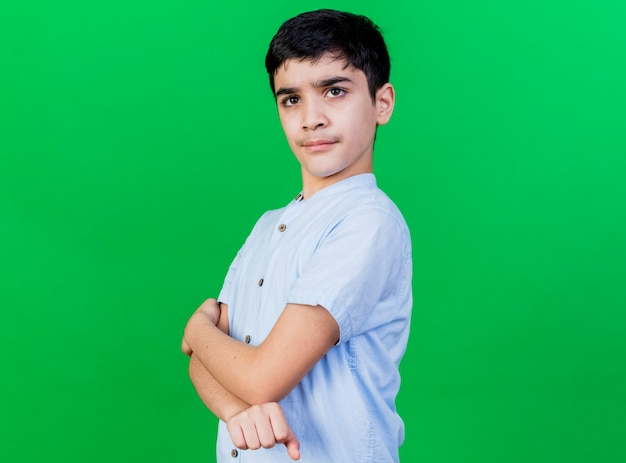 Confident young boy standing with closed posture in profile view looking at front isolated on green wall