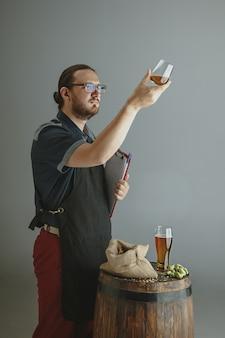 회색 배경에 있는 나무 통에 유리에 직접 만든 맥주를 넣은 자신감 있는 젊은 양조업자. 공장 소유주가 양조 제품을 선보이고 품질을 테스트했습니다. 옥토버 페스트, 음료, 알코올.