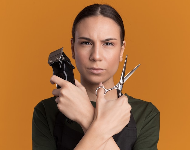 Confident young brunette barber girl in uniform holds hair thinning scissors and hair clippers