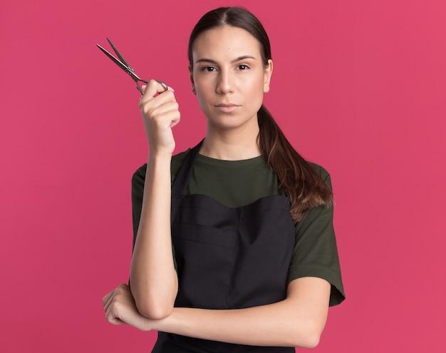 La giovane ragazza barbiere bruna sicura in uniforme tiene le forbici per sfoltire i capelli isolate sulla parete rosa con lo spazio della copia