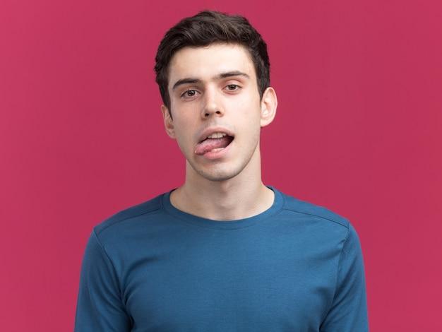 自信を持って若いブルネットの白人の少年は、カメラを見て舌を突き出します