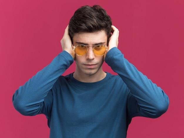 Fiducioso giovane brunetta caucasico ragazzo con gli occhiali da sole mette le mani sulle orecchie guardando la telecamera