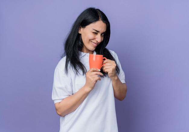 자신감이 젊은 갈색 머리 백인 여자는 눈을 깜박이고 보라색 벽에 고립 된 찾고 컵을 보유
