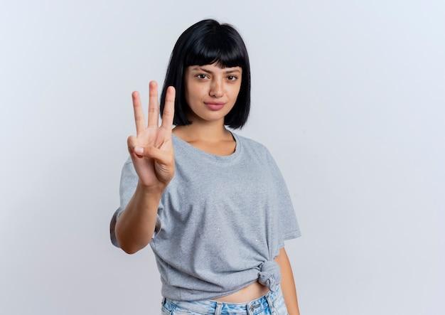 Уверенная молодая брюнетка кавказская девушка жесты три