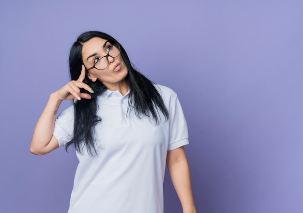 光学メガネで自信を持って若いブルネットの白人の女の子は、紫色の壁に孤立して見上げる寺院に指を置きます