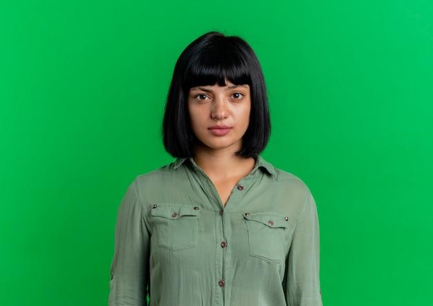 Fiduciosa giovane ragazza bruna caucasica guarda la telecamera isolata su sfondo verde con spazio di copia