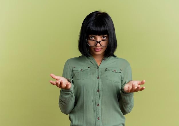 Fiduciosa giovane ragazza caucasica bruna in vetri ottici tiene le mani aperte alla ricerca