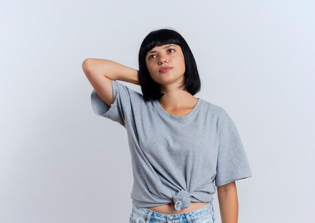 Fiduciosa giovane ragazza bruna caucasica mette la mano sulla testa dietro guardando a lato