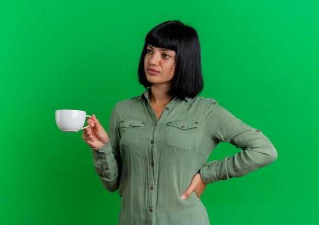La giovane ragazza caucasica castana sicura mette la mano sulla vita e tiene la tazza che esamina il lato isolato su fondo verde con lo spazio della copia