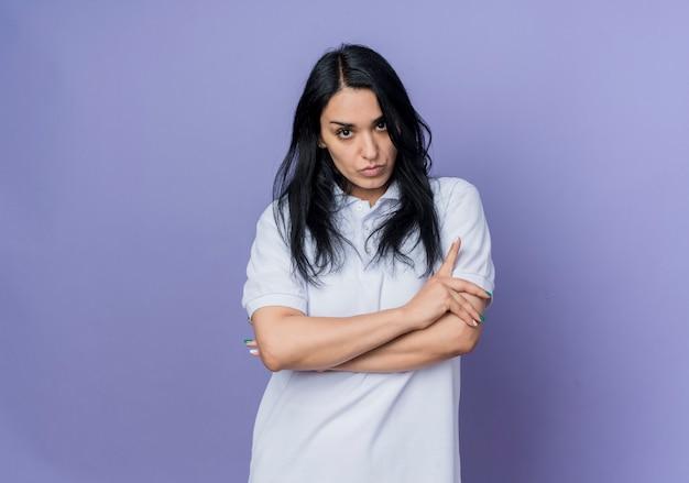 자신감이 젊은 갈색 머리 백인 여자는 보라색 벽에 고립 된 교차 팔 스탠드