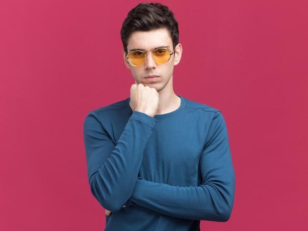 Il giovane uomo caucasico castana sicuro in occhiali da sole mette il pugno sul mento isolato sulla parete rosa con lo spazio della copia
