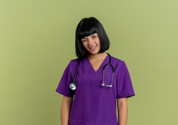 Fiducioso giovane dottoressa bruna in uniforme con lo stetoscopio lampeggia gli occhi guardando la telecamera isolata su sfondo verde oliva con lo spazio della copia