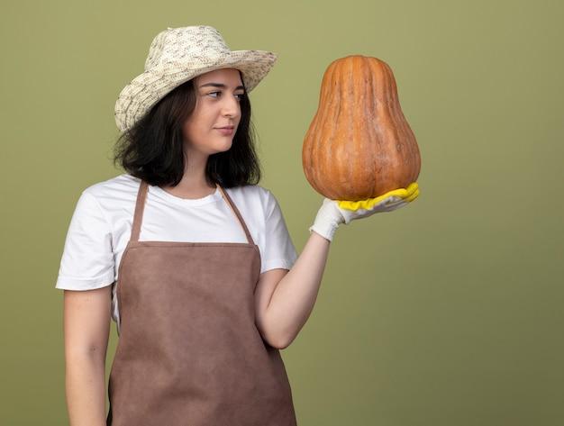Уверенная молодая брюнетка женщина-садовник в униформе в садовой шляпе и перчатках держит и смотрит на тыкву, изолированную на оливково-зеленой стене