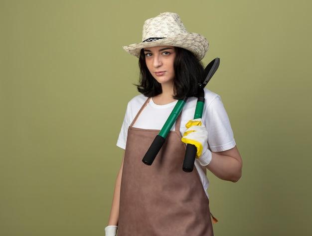 Уверенная молодая брюнетка женщина-садовник в униформе в садовой шляпе и перчатках держит садовые ножницы на плече, изолированные на оливково-зеленой стене
