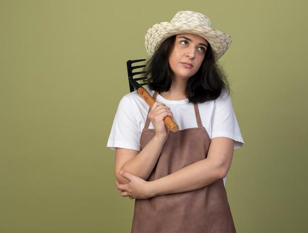 Уверенная молодая брюнетка женщина-садовник в униформе в садовой шляпе держит грабли на плече и смотрит на сторону, изолированную на оливково-зеленой стене