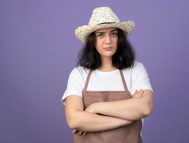 ガーデニング帽子を身に着けている制服を着た自信を持って若いブルネットの女性の庭師は、紫色の壁で隔離の腕を組んで立っています