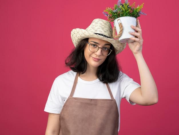 Il giovane giardiniere femminile castana sicuro in vetri ottici e in uniforme che indossa il cappello da giardinaggio tiene il vaso di fiori sopra la testa isolata sulla parete rosa