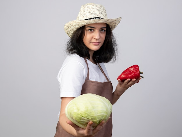 Il giovane giardiniere femminile castana sicuro in cappello da giardinaggio d'uso uniforme tiene il cavolo ed i peperoni rossi isolati sulla parete bianca
