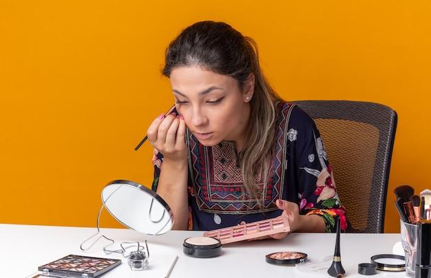 Уверенная молодая брюнетка девушка сидит за столом с инструментами для макияжа, применяя тени для век с кистью для макияжа, глядя в зеркало