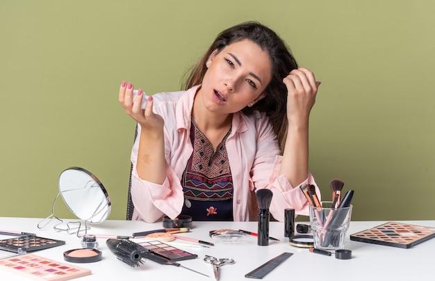 Уверенная молодая брюнетка девушка сидит за столом с инструментами для макияжа, держа мусс для волос, изолированные на оливково-зеленой стене с копией пространства