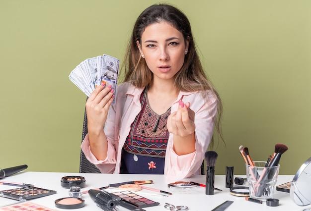 Уверенная молодая брюнетка девушка сидит за столом с инструментами для макияжа, держит деньги и жестикулирует знак денег, изолированные на оливково-зеленой стене с копией пространства