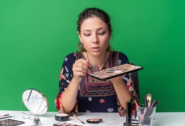 La giovane ragazza castana sicura che si siede alla tavola con gli strumenti di trucco tiene e guarda la tavolozza dell'ombretto e il pennello di trucco isolati sulla parete verde con lo spazio della copia