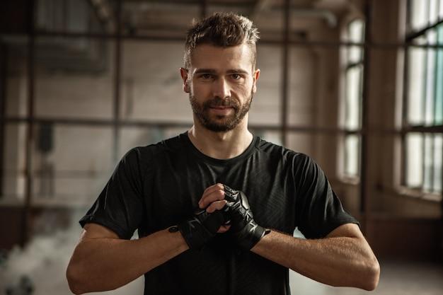 Уверенный молодой брутальный боксер-мужчина в черной футболке и защитных перчатках греет руки и смотрит перед тренировкой