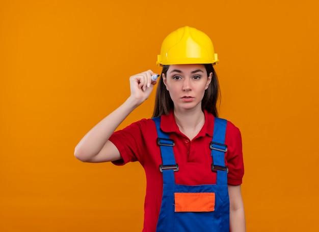 自信を持って若いビルダーの女の子は、コピースペースで孤立したオレンジ色の背景にマーカーを保持します