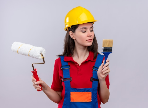 Confident young builder girl holds paint roller and paint brush on isolated white background