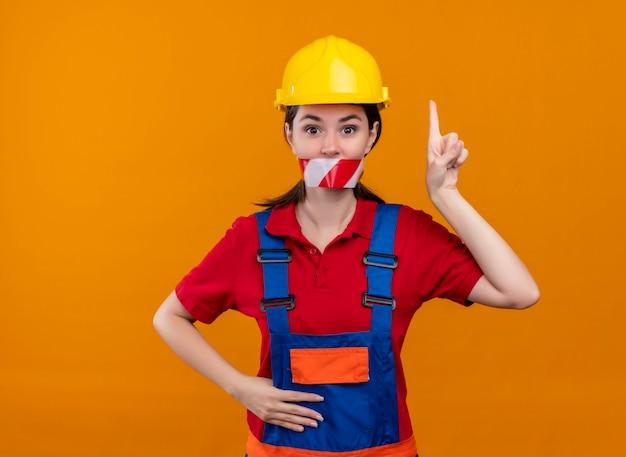Уверенная молодая девушка-строитель заклеила рот предупреждающей лентой и указывает вверх на изолированный оранжевый фон