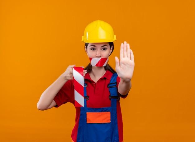 La bocca sicura della ragazza del giovane costruttore sigillata con il nastro di avvertimento tiene il nastro e mostra il gesto di arresto su fondo arancio isolato con lo spazio della copia