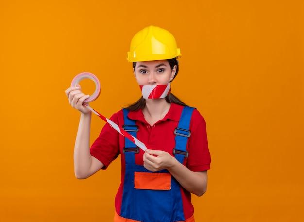 La bocca sicura della ragazza del giovane costruttore sigillata con nastro adesivo di avvertenza tiene il nastro con entrambe le mani su fondo arancio isolato