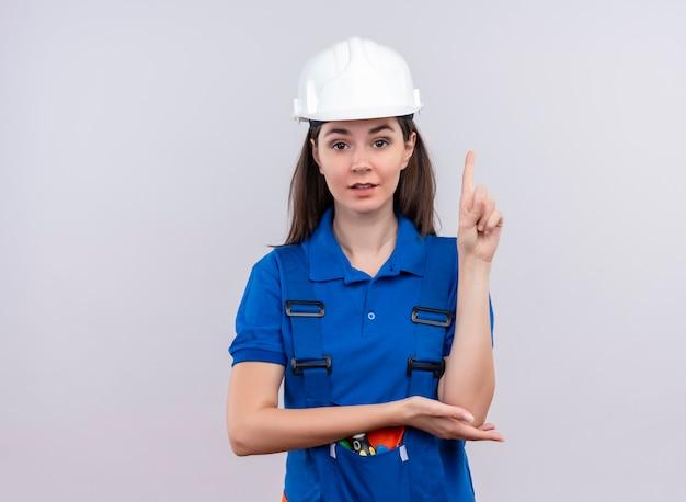 흰색 안전 헬멧과 파란색 유니폼과 자신감이 젊은 작성기 소녀 복사 공간이 격리 된 흰색 배경에 포인트