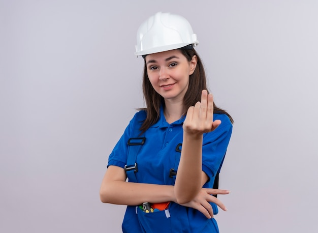 Уверенная молодая девушка-строитель в белом защитном шлеме и синей форме делает вид, что звонит кому-то на изолированном белом фоне с копией пространства