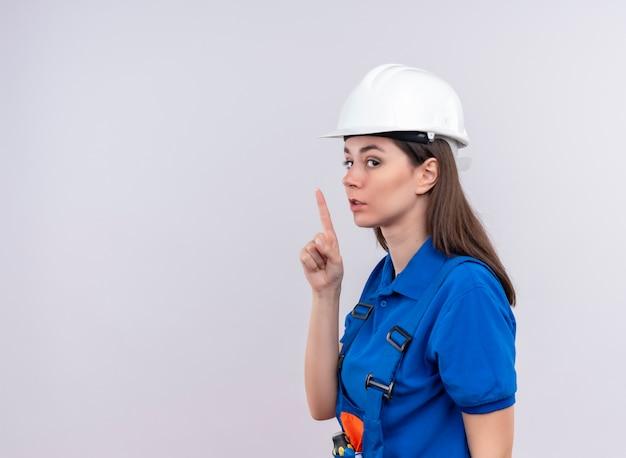 흰색 안전 헬멧과 파란색 유니폼과 자신감이 젊은 작성기 소녀는 옆으로 스탠드와 복사 공간이 격리 된 흰색 배경에 침묵의 제스처