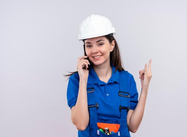 Уверенная молодая девушка-строитель с белым защитным шлемом и синей униформой разговаривает по телефону и жестикулирует в знак рогов на изолированном белом фоне с копией пространства