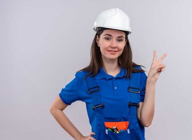 Ragazza fiduciosa del giovane costruttore con casco di sicurezza bianco e segno di vittoria di gesti uniformi blu e mette la mano sulla vita su fondo bianco isolato con lo spazio della copia