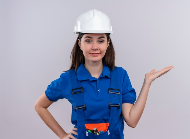 Fiducioso giovane ragazza costruttore con casco di sicurezza bianco e uniforme blu tiene la mano e mette la mano sulla vita su sfondo bianco isolato con spazio di copia