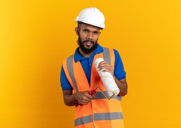 Fiducioso giovane costruttore uomo in uniforme con casco di sicurezza tenendo il rullo di vernice isolato sulla parete arancione con copia spazio