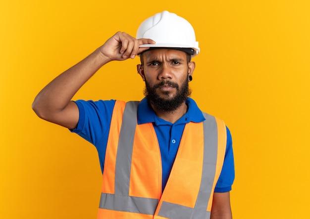 Fiducioso giovane costruttore uomo in uniforme con casco di sicurezza mettendo la mano sul casco isolato sulla parete arancione con copia spazio